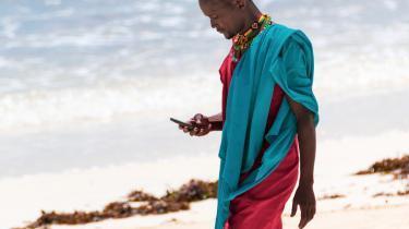 Man_with_phone_on_beach.jpg